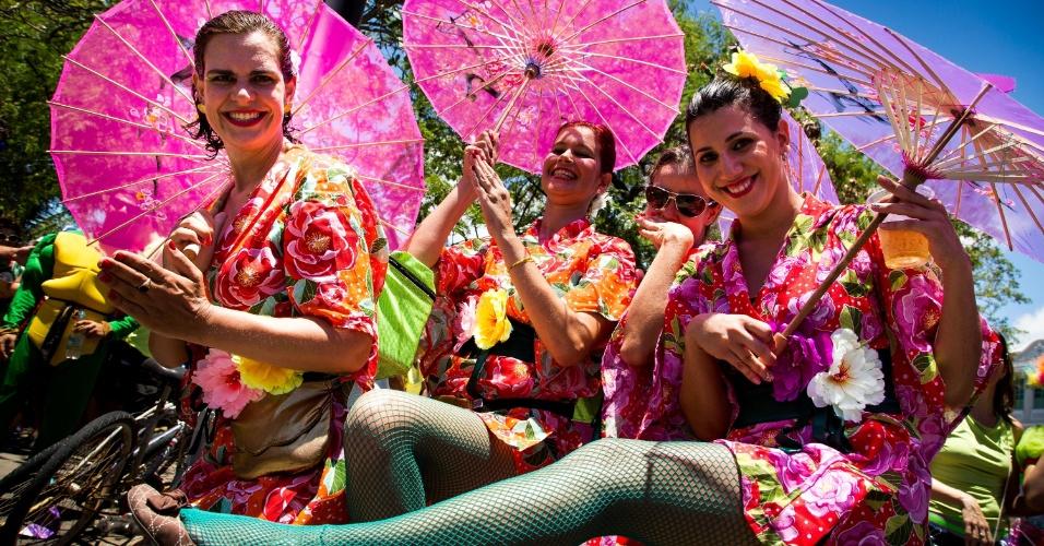 2.mar.2014 - Gueixas tropicais aproveitam as sombrinhas das fantasias para se protegerem do calor em Olinda (PE)
