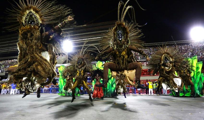 2.mar.2014 - Integrantes da Império da Tijuca pulam na Sapucaí durante o desfile da escola