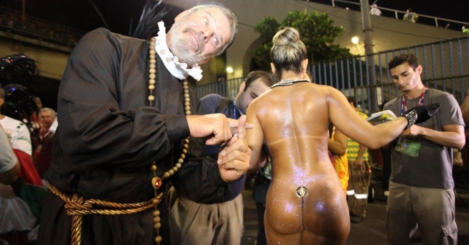 2.mar.2014 - Vestido de padre, Raul Gazolla posa à frente da Mulher Melão na concentração da Grande Rio