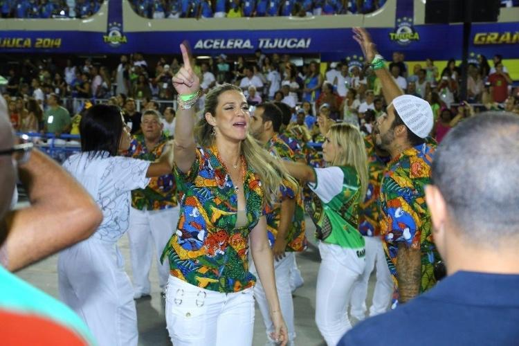 3.mar.2014 - Luana Piovani e Pedro Scooby fazem o tradicional passo de dança de samba com indicadores para cima; com um problema no joelho, ela não pôde ser destaque de carro