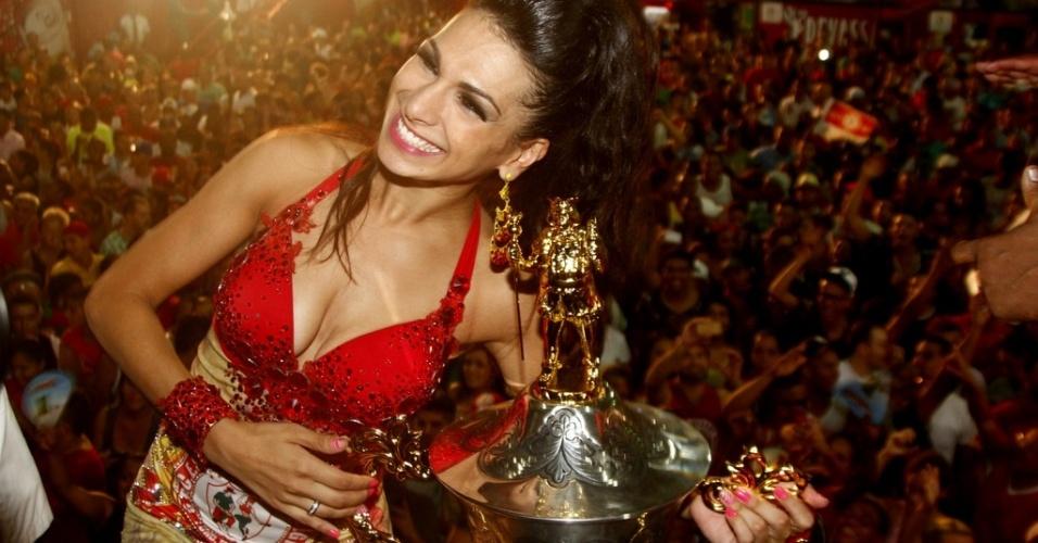 4.mar.2014 - A rainha de bateria da Mocidade Alegre, Aline Oliveira, ao lado da taça de campeã do Carnaval paulistano