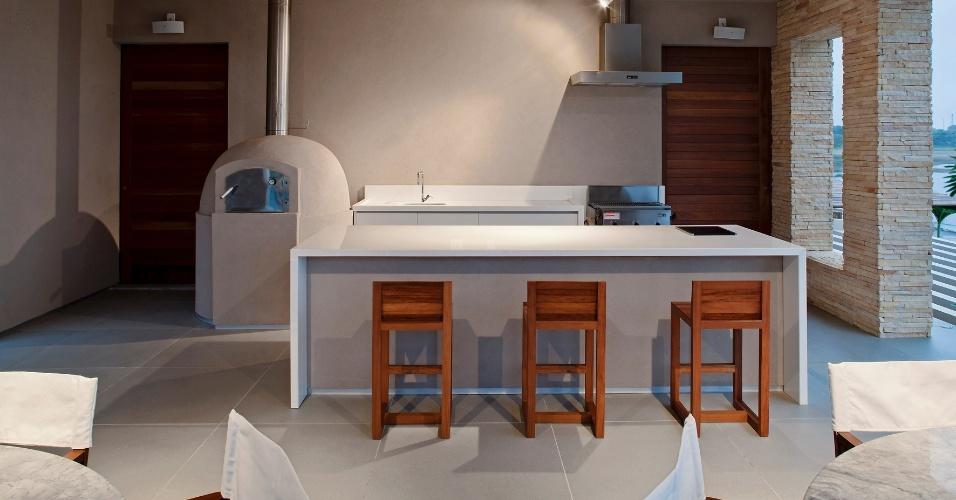 O espaço gourmet integrado à varanda é dotado dos apetrechos necessários para as reuniões de amigos. Como forno de pizza, chapa e balcão com banquetas. A Casa da Praia dos Lagos foi projetada pelo escritório Sotero Arquitetos