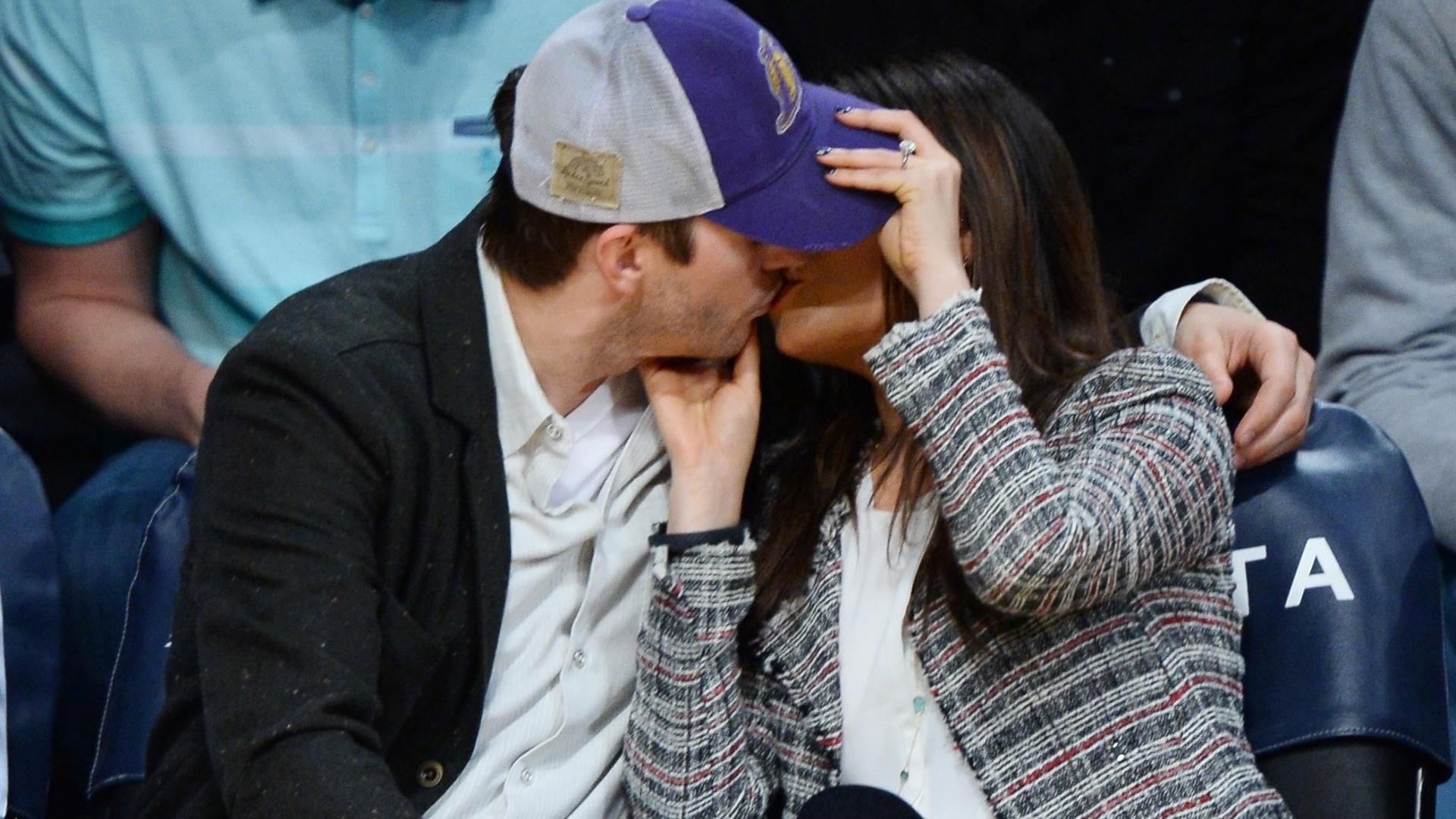 5.mar.2014- Ashton Kutcher e Mila Kunis se beijam no jogo do Los Angeles Lakers, em Los Angeles. o casal foi flagrado sorrindo no momento de lazer e a atriz exibiu seu anel de noivado