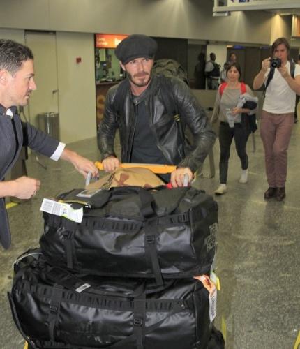 6.mar.2014 - No Brasil para assistir aos desfiles das escolas campeãs do Rio de Janeiro, o jogador de futebol David Beckham é assediado no aeroporto
