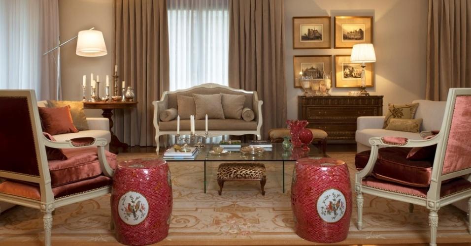 Esta sala de estar (32 m²) projetada pelo arquiteto Maurício Karam recebeu estofados neutros com desenho reto, poltronas de madeira renovadas pela laca brilhante e revestidas de veludo bordô, além do sofá que segue a mesma linha de acabamento e os móveis rebuscados que mantiveram o tom original da madeira. O conjunto ficou chique com ligeiro toque provençal.