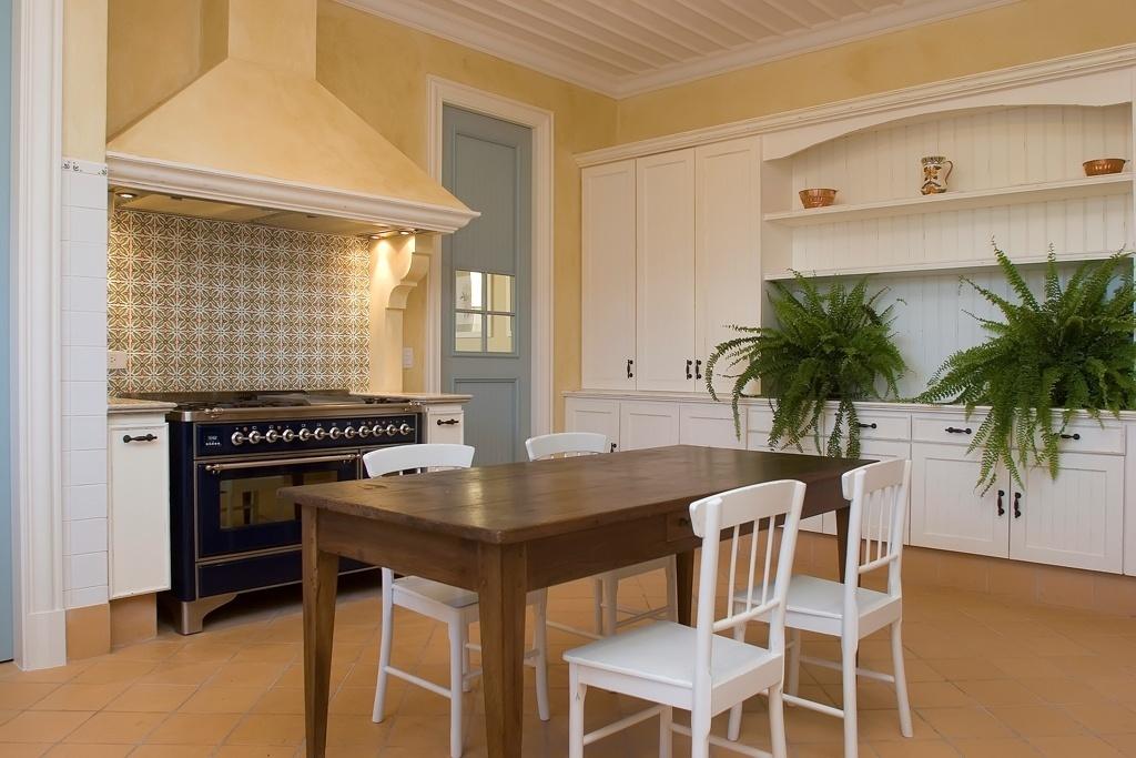 Na cozinha (30 m²), o branco dos armários (Fabricca Marcenaria) e das cadeiras contrasta com o tom da mesa em madeira encerada, o fogão com design retrô e o piso cerâmico. O azulejo antigo, na área de cocção, marca o ambiente através de sua estampa floral. O projeto de decoração é assinado por Leonardo Junqueira