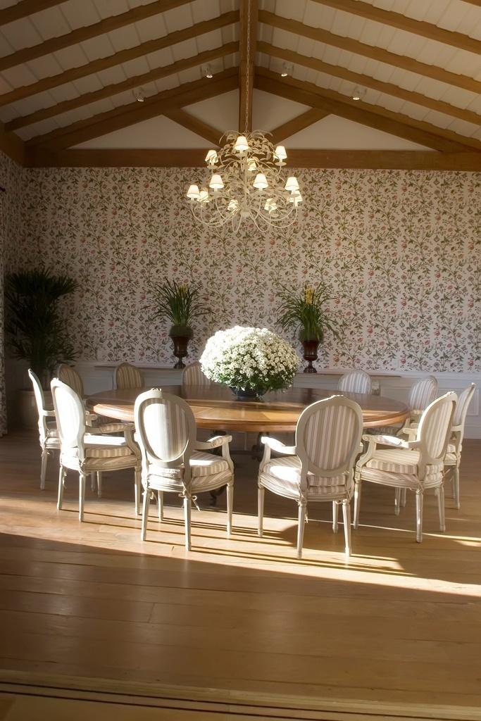 Nesta sala de jantar (40 m²), idealizada por Leonardo Junqueira, o clima provençal está completo. A vedete é o papel de parede floral (Prints), que dá o tom rural, suavizando o piso de canela de demolição e as tesouras aparentes do telhado. A grande mesa redonda de madeira antiga se alinha às poltronas medalhão patinadas e revestidas por tecido listrado