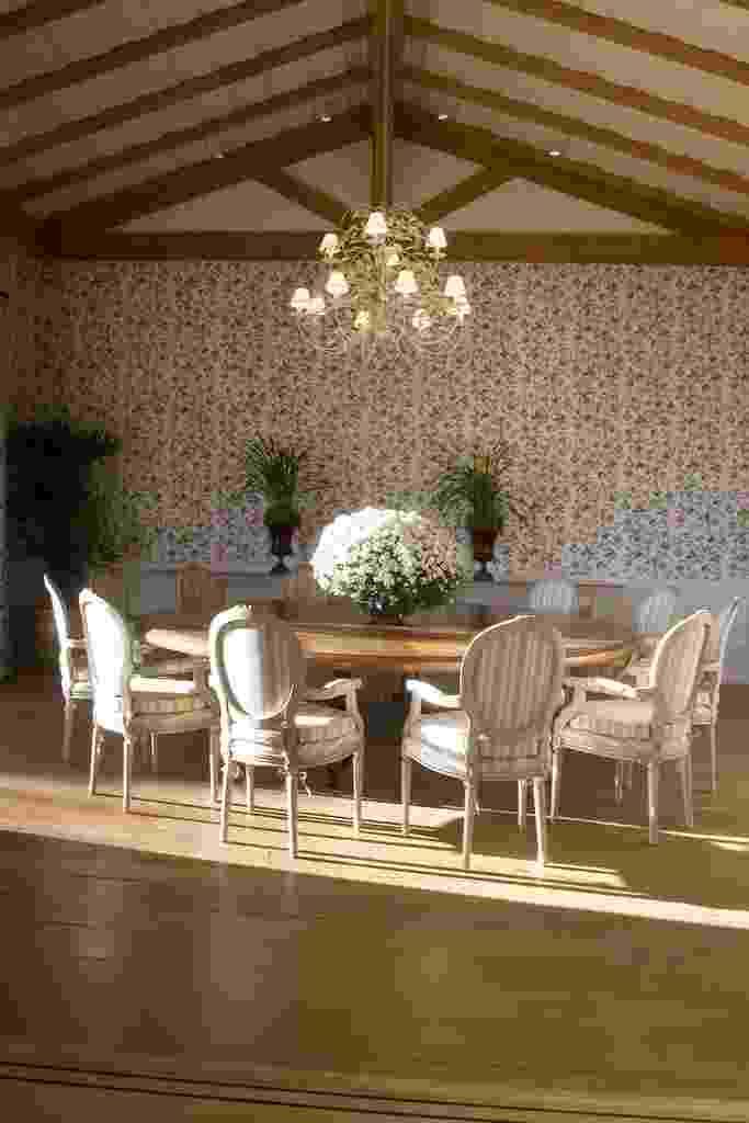 Nesta sala de jantar (40 m²), idealizada por Leonardo Junqueira, o clima provençal está completo. A vedete é o papel de parede floral (Prints), que dá o tom rural, suavizando o piso de canela de demolição e as tesouras aparentes do telhado. A grande mesa redonda de madeira antiga se alinha às poltronas medalhão patinadas e revestidas por tecido listrado - J. Vilhora/ Divulgação