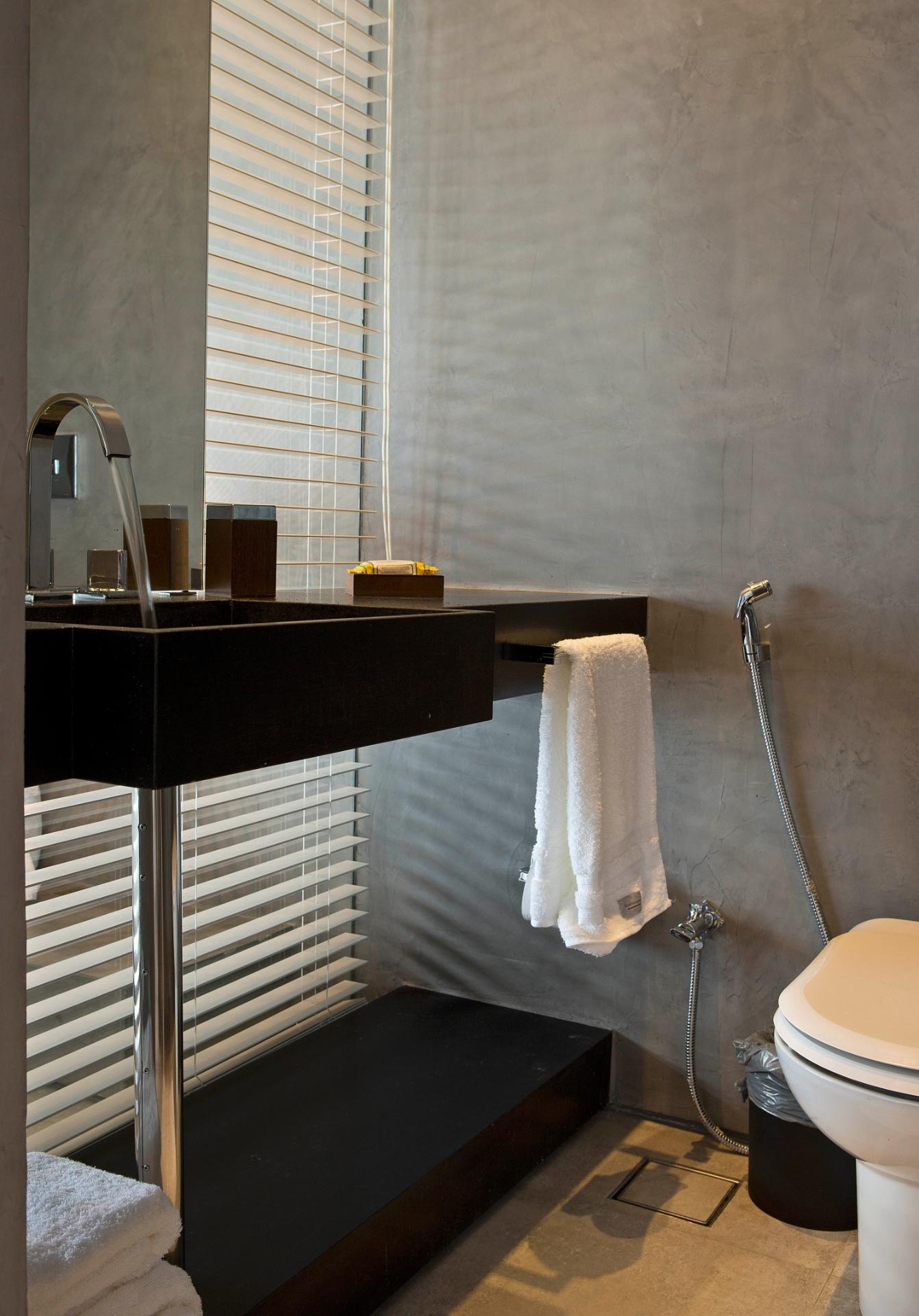 O cimento queimado reveste as paredes do banheiro da suíte e é harmonizado com o granito preto da bancada e com as persianas prata, da Uniflex. A cobertura Rio Design Leblon tem projeto de reforma assinado pelo escritório House in Rio