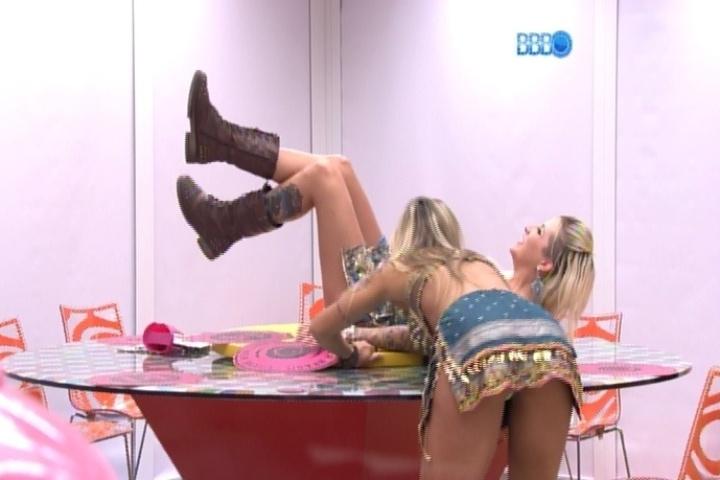 16.mar.2014 - Clara sobe na mesa da casa-grande e roda no suporte central. Vanessa acha que não deveriam estar fazendo isso.
