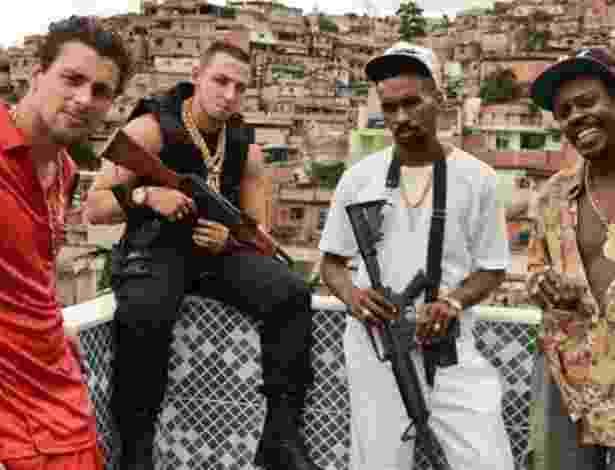 """Cauã Reymond e o funkeiro MC Smith (de preto, com arma na mão) em imagem do filme """"Alemão"""" - Divulgação"""