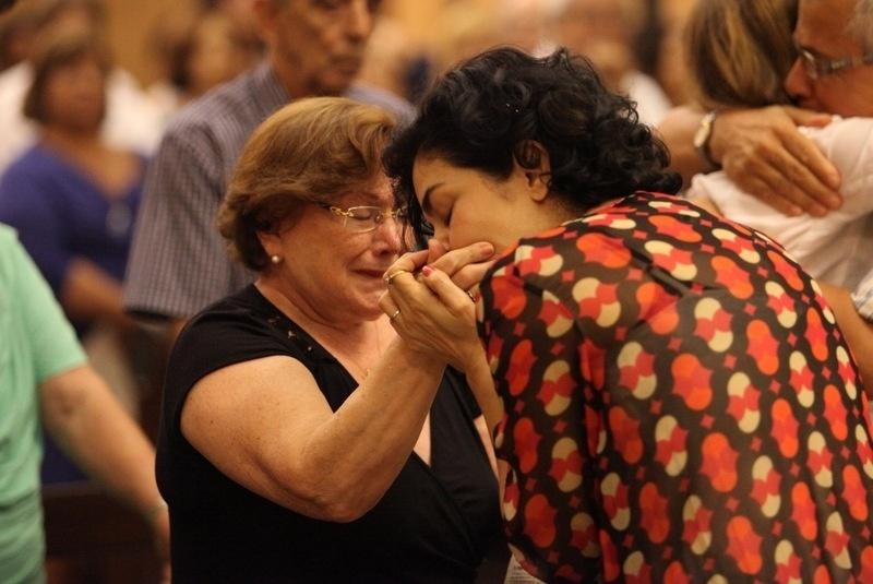 20.mar.2014 - Letícia Sabatella beija a mãe de Nicette Bruno na missa de sétimo dia da morte do ator Paulo Goulart, na Igreja Nossa Senhora da Paz, em Ipanema, no Rio