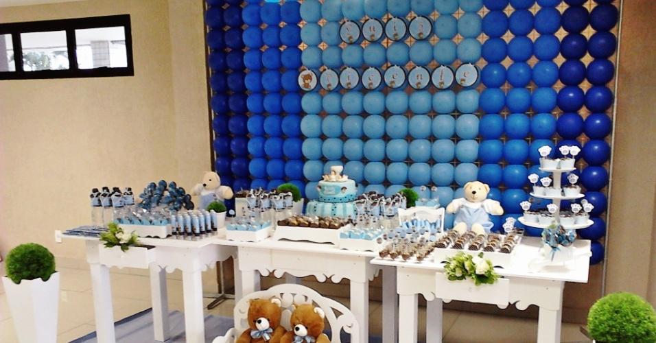 Na decoração com o tema Ursinhos, feita pela empresa Eva Decor (http://evadecor.blogspot.com.br/), um painel de alumínio com bexigas em tons de azul foi posicionado atrás da mesa principal. Os doces e o bolo, produzidos nas mesmas cores, foram posicionados em suportes de MDF branco. Os adesivos que imitam pegadas de urso ajudam a deixar o ambiente ainda mais lúdico e divertido