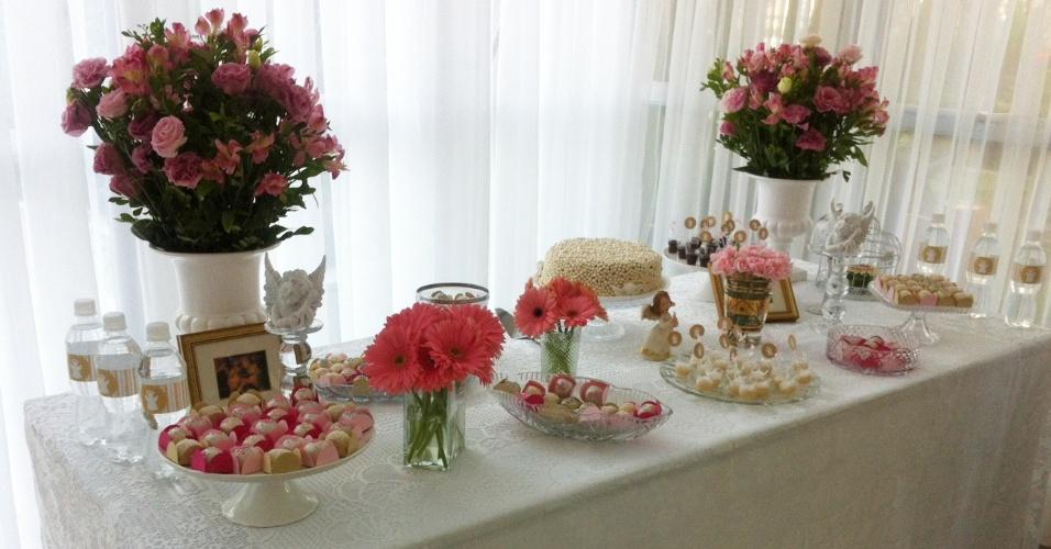 Na mesa decorada por Andrea Constantino, o destaque fica por conta das flores: cravos, rosas, gérberas e astromélias. O bolo de doce de leite foi coberto com confeitos de chocolate branco e os doces foram acomodados em forminhas nas cores rosa, pink e amarelo