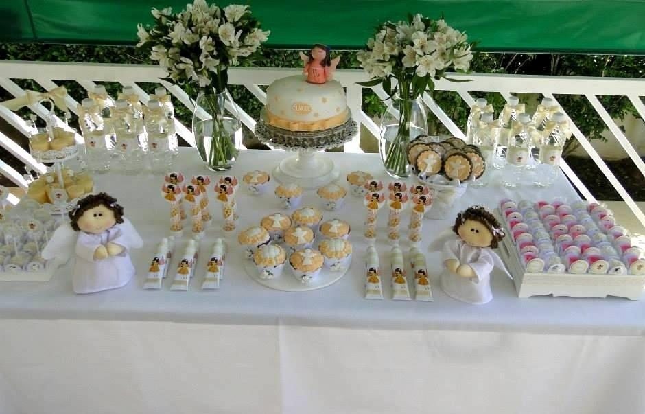 Os anjinhos também aparecem na ambientação criada pela Delicatto (http://delicattofestas.blogspot.com.br/) para este batizado, realizado em uma residência. Os da mesa foram confeccionados em feltro e, no topo do bolo, o anjinho é de pasta americana. Pirulitos, cupcakes, bisnagas de brigadeiro e outras guloseimas acompanham o tema da festa