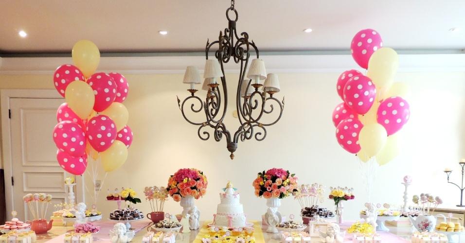 As cores predominantes na decoração, o rosa e o amarelo, dão unidade aos diversos elementos utilizados. Na mesa, montada sobre peças de porcelanato, os arranjos florais, feitos com rosas mescladas, begônias e hortênsias, ficam em evidência. A ambientação foi feita em uma residência, pela Mania de Fita (http://www.maniadefita.com.br/)