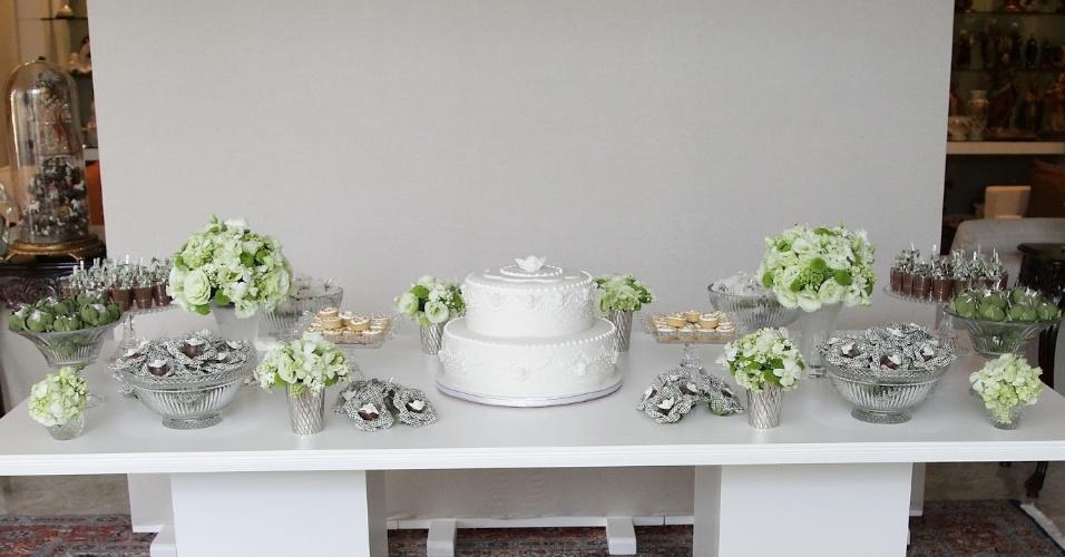 O branco se destaca na mesa montada na sala de uma residência por Kely Pinheiro (http://www.blogbellafiore.com/). A decoração sofisticada tem arranjos de lisiantos, bombons e bem-nascidos envolvidos em retalhos de tecido verde. O resultado é uma ambientação que casa muito bem com as peças mais escuras que já faziam parte do cômodo e que aparecem ao fundo