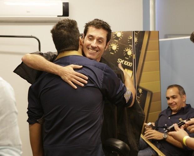 26.mar.2014 - Dinho Ouro Preto e André Marques se abraçam momentos antes da coletiva do