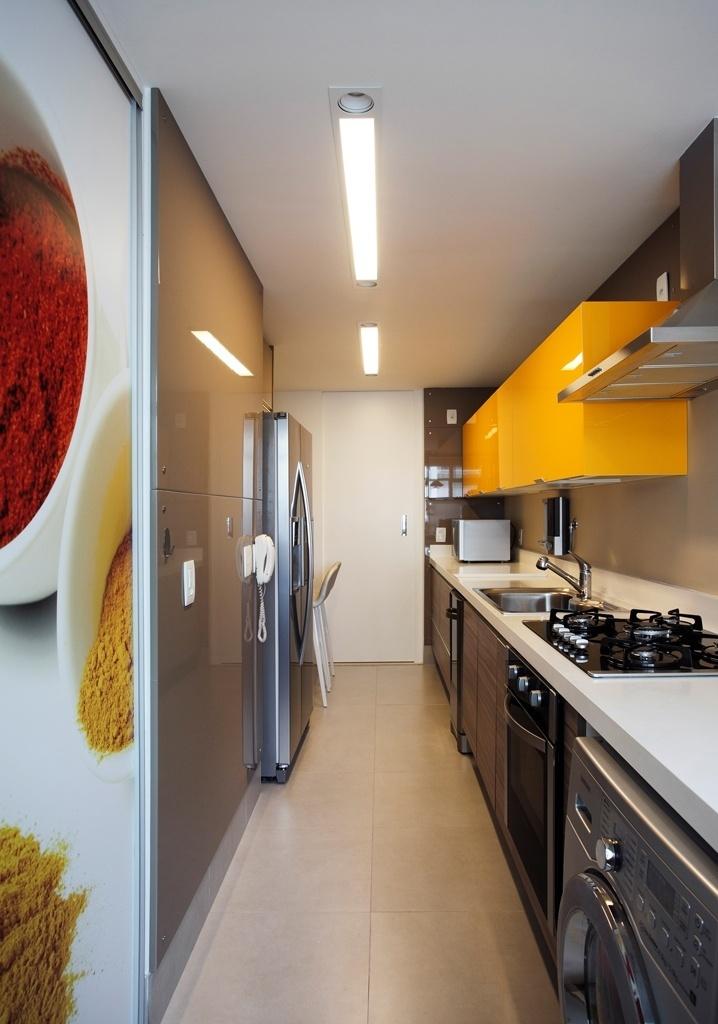 Com 15 m², a cozinha desse apartamento, no Rio de Janeiro (RJ), pode ser vista da sala e, por isso mesmo, recebeu acabamentos sofisticados, como vidro colorido no armário sobre a bancada (Cinex), painéis de forração das paredes em laca alto brilho (Favo) e bancada contínua em quartzo. A arquiteta Iolanda Miguel Vieira, do escritório Insight Arquitetura, conta que a escolha pelo amarelo se deu para trazer luz e calor ao ambiente
