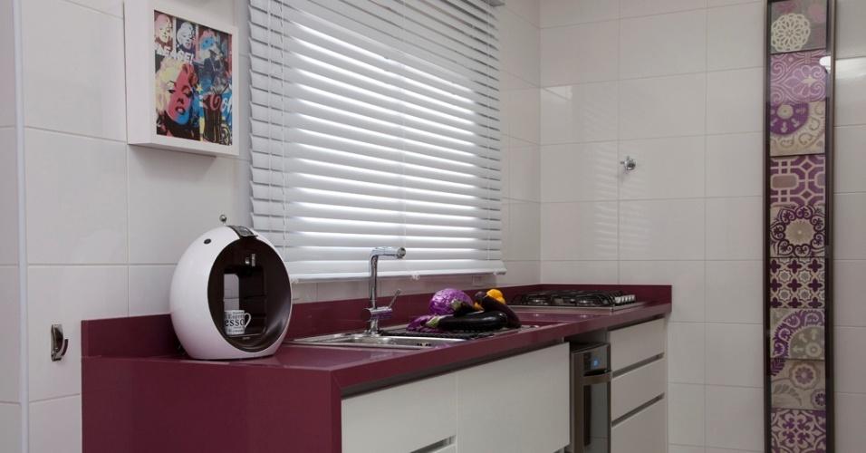 Para a cozinha desse apartamento em São Caetano do Sul (SP), as arquitetas Cinthia Garcia e Andréia Karalkovas optaram pelo tom berinjela. Em harmonia com o branco dos armários, a cor aparece com intensidade na bancada em silestone koan, executada pela Navona Mármores