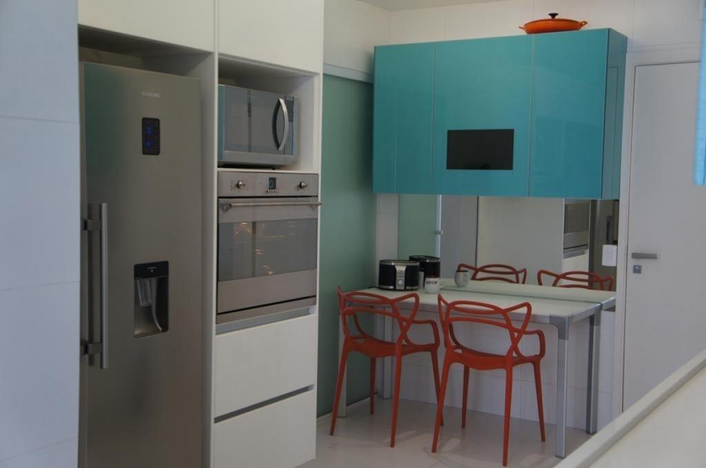 Para os moradores desse apartamento na Barra da Tijuca, no Rio de Janeiro (RJ), a cozinha é o espaço mais importante da casa. Para prover uma atmosfera mais jovial e alegre, o projeto da arquiteta Fátima Freire, apostou na combinação de armários com portas laqueadas azuis (Favo Móveis), eletrodomésticos em aço inox e acessórios laranja