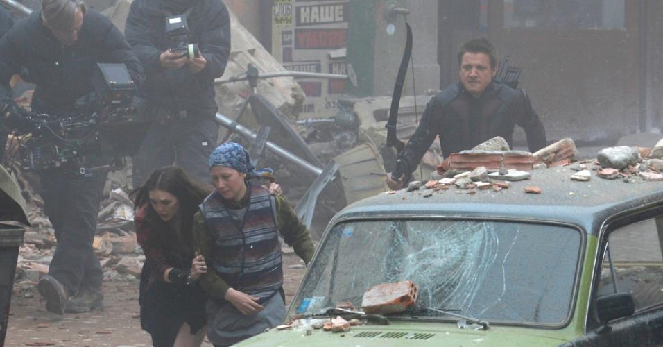 27.mar.2014 - Os atores Elizabeth Olsen (à frente) e Jeremy Renner são vistos em ação, gravando cenas para o mais novo filme da Marvel,