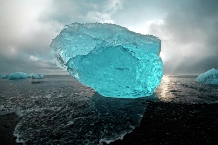 """Sam Morris registrou este iceberg no Atlântico Norte. """"A maré cria uma magnífica galeria de enormes esculturas de gelo nas praias vulcânicas negras da Islândia"""", diz o fotógrafo"""
