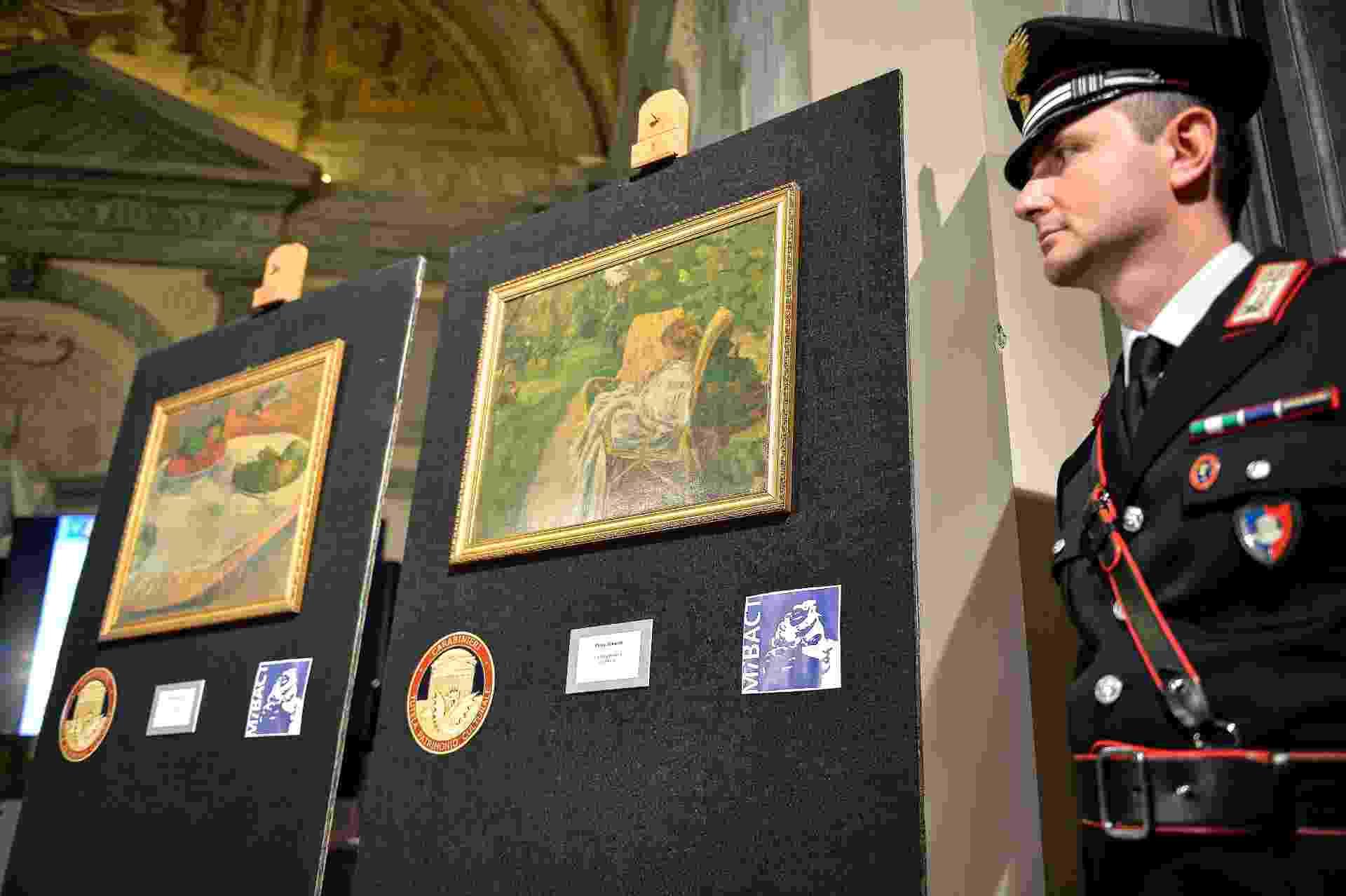 2.abr.2014 - Carabineiro é fotografado ao lado de obras de Paul Gauguin e Pierre Bonnard, recuperadas na Itália após roubo em Londres, nos anos 1970 - Andreas Solaro/AFP