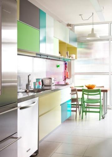 Deste ângulo, avista-se a porta de vidro que separa a cozinha da lavanderia, além da mesa com cadeiras coloridas para pequenas refeições. O apartamento RO tem projeto de reforma do SuperLimão Studio