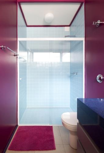 O banheiro dos hóspedes é composto por cores intensas, na quase totalidades das paredes e na porta, o rosa está, inclusive, na moldura do forro com rebaixo em gesso. Para amenizar o impacto das cores quentes, a área molhada foi revestida por azulejos em um azul delicado. O projeto para o apê RO, que venceu o prêmio