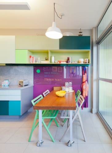 Um simpático recanto da cozinha foi destinado às pequenas refeições. Nele, a mesa com rodízios foi combinada às cadeiras em verde e