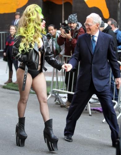 2.abr.2014 - De calcinha, sutiã e jaqueta, Lady Gaga anda por rua de Nova York de mãos dadas o apresentador David Letterman após gravar uma participação no