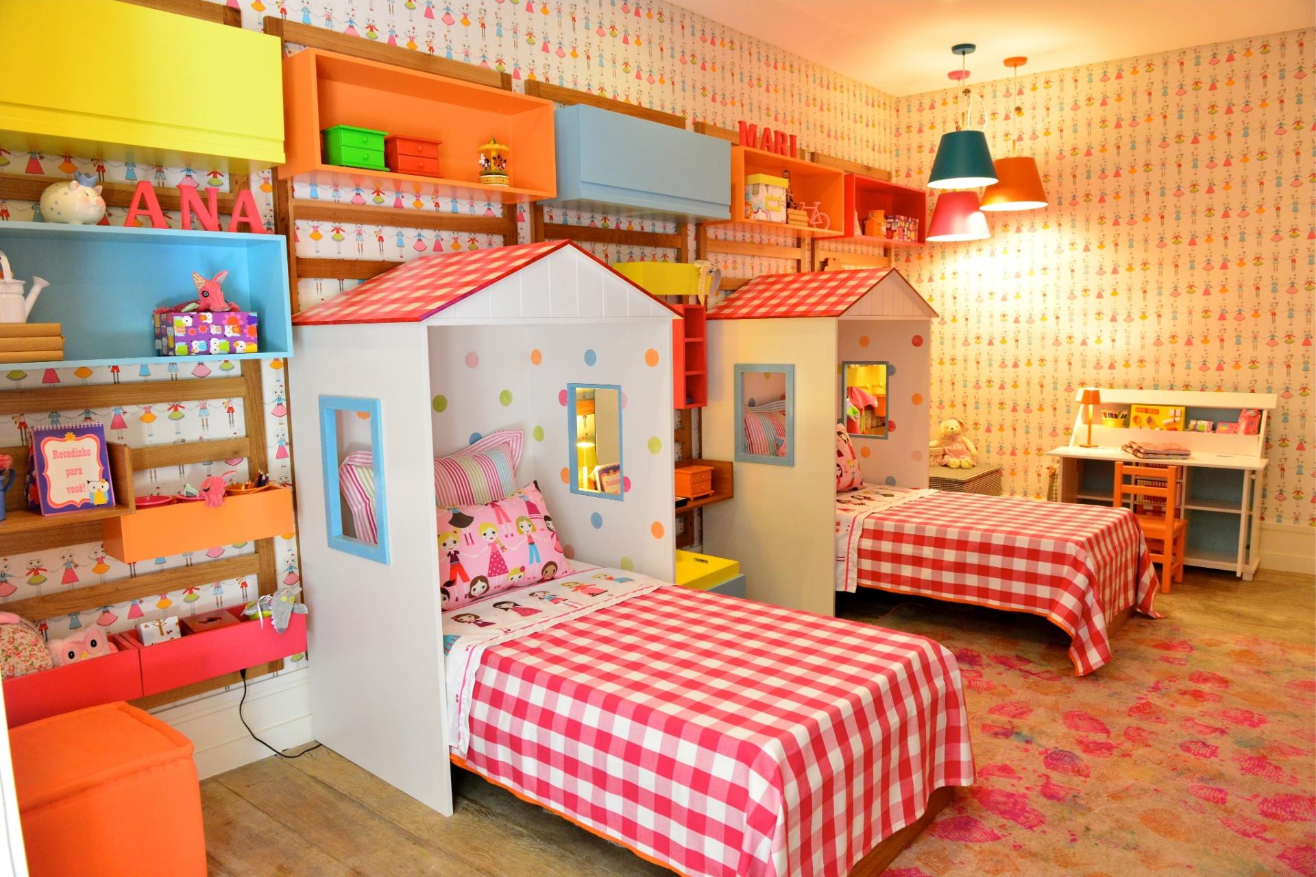 Desenvolvido pelos arquitetos Carmen Mansor, Fernando Azevedo e Tiza Kann, este quarto com 17 m², para duas meninas em idade escolar, é puro estímulo. A intenção foi aguçar os sentidos usando cores fortes e inventando essa brincadeira das camas em forma de cabanas, afirmam os profissionais. No ambiente, algumas áreas são compartilhadas como a escrivaninha e os nichos para brinquedos. O mobiliário é da Q&E Bebê; o papel de parede, da Orlean; e as luminárias coloridas, da Lumini
