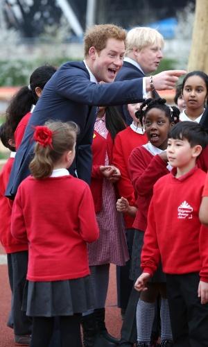 4.abr.2014 - Príncipe Harry conversa com grupo de crianças durante visita oficial ao Queen Elizabeth Olympic Park, em Londres