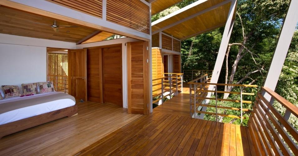 A suíte menor está no terceiro módulo que compõe a casa Flotanta (fundo), em bloco um pouco mais recuado e sombreado. A varanda faz conexão com o dormitório principal, que repete o padrão arquitetônico da ala social. Sua característica principal são aberturas frontais totais, com portas-camarão (venezianas) para a varanda (em primeiro plano). A residência tem projeto de Benjamin Garcia Saxe, em Puntarenas, Costa Rica