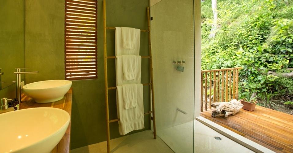 Apesar de ser o cômodo mais privativo da casa Flotanta, o banheiro da suíte máster tem um boxe que se abre para a varanda coberta e para a encosta verde do morro, que tange a residência aos fundos. A única divisão entre banho e pias está em uma folha simples de vidro temperado. O projeto de Benjamin Garcia Saxe fica na Costa Rica