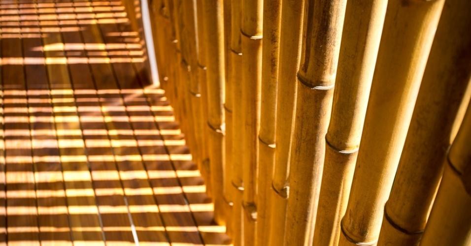 As paredes do corredor são semiabertas pela estruturação em bambu. O recurso dá vazão ao sol, de forma que a parte  posterior da casa Flotanta, junto à encosta verde de um morro, receba luz natural. A residência está em Puntarenas, na Costa Rica, e tem design da equipe do arquiteto Benjamin Garcia Saxe