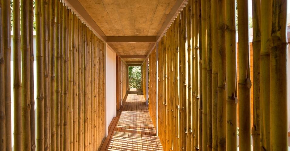 Um corredor semiaberto com paredes de bambu faz a circulação entre os cômodos da casa Flotanta, em Puntarenas, na Costa Rica. Por entre os bambus avista-se, à direita, o Oceano Pacífico e, à esquerda, a vegetação densa tropical das montanhas. No espaço, forro e piso são em madeira, no projeto arquitetônico de Benjamin Garcia Saxe