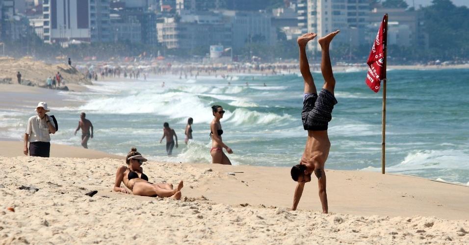 11.abr.2014 - Ao lado de Fernanda Lima, Rodrigo Hilbert planta bananeira na praia do Leblon, na zona sul do Rio. O casal estava acompanhados dos filhos gêmeos João e Francisco