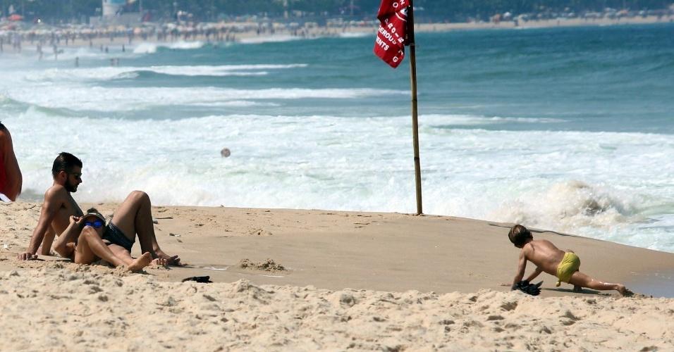 11.abr.2014 - Deitada no colo de Rodrigo Hilbert, Fernanda Lima se bronzeia na praia do Leblon, na zona sul do Rio. O casal estava acompanhados dos filhos gêmeos João e Francisco