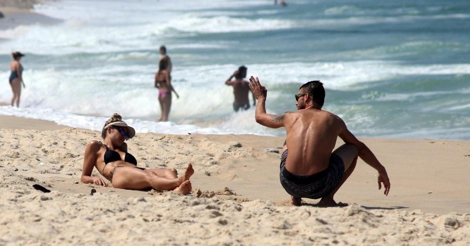 11.abr.2014 - Fernanda Lima e Rodrigo Hilbert se bornzeiam na praia do Leblon, na zona sul do Rio. O casal estava acompanhados dos filhos gêmeos João e Francisco