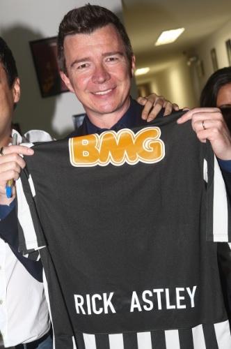 """11.abr.2014 - Antes de começar seu show, Rick Astley recebe fãs em seu camarim e ganha de um deles uma camisa do Santos. Esta é a primeira vez que ele se apresenta no país e fez sua estreia no HSBC Brasil, na zona sul de São Paulo, na noite desta sexta-feira, cantando seu repertório que fez grande sucesso nos anos 1980 e 1990, como """"Never Gonna Give You Up"""" e """"Hold Me In Your Arms"""". Em 2008, o britânico voltou à mídia após virar um meme na internet chamado """"Rickrolling"""""""