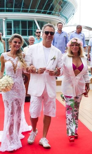 13.abr.2014 - Vestindo uma camisa branca aberta, um sutiã rosa e uma coroa de flores na cabeça, Susana Vieira acompanha os noivos ao fim da cerimônia