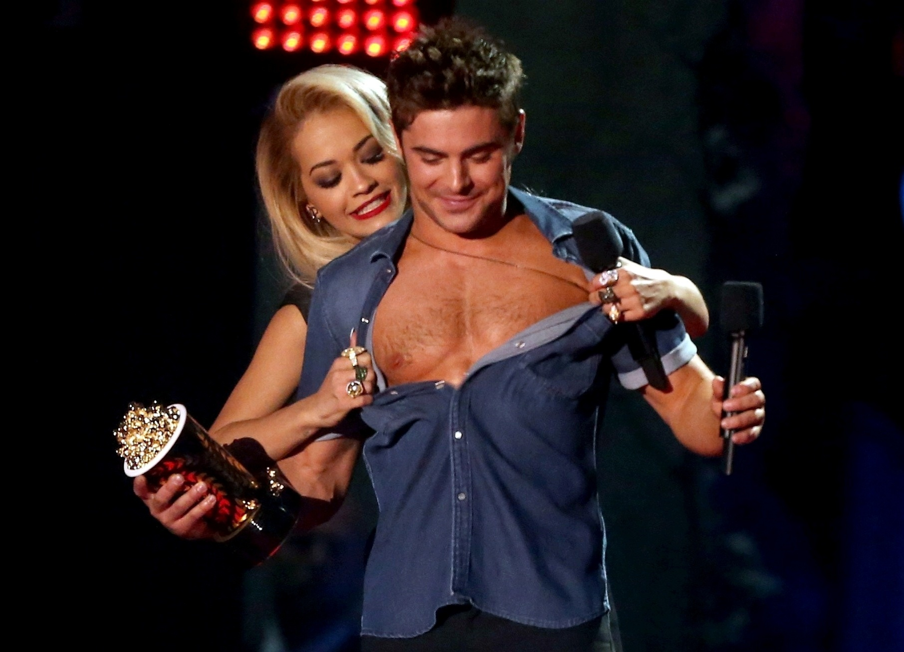 13.abril.2014 - Rita Ora tira a camisa de Zac Efron no MTV Movie Awards 2014, na noite deste domingo (13), no Nokia Theatre, em Los Angeles