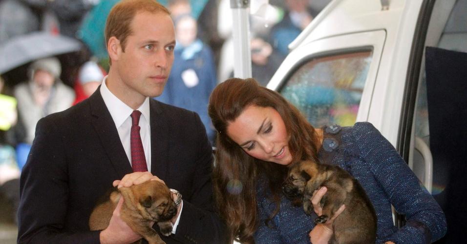 16.abr.2014 - Príncipe William e Kate Middleton posam com filhotes de cachorros durante visita à Royal New Zealand Police College, a academia de polícia real na Nova Zelândia. O casal está em viagem pela Oceania, a primeira acompanhado pelo filho, George