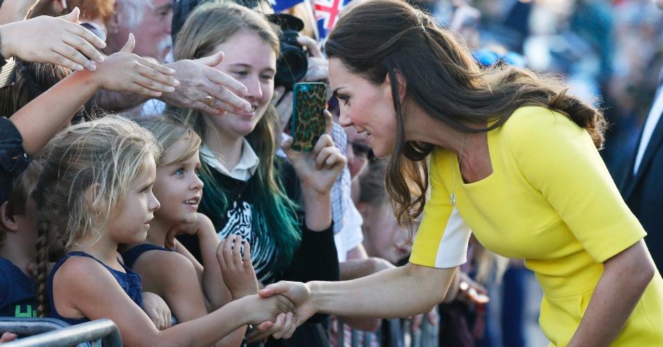 16.abr.2014 - Kate Middleton cumprimenta menina ao ser recebida por multidão na Royal Opera House, em Sidney. A Duquesa de Cambridge e o marido desembarcaram nesta quarta-feira na cidade australiana