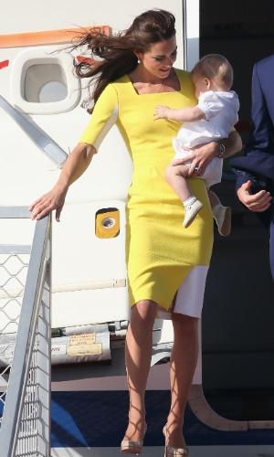 16.abr.2014 - Kate Middleton desembarca com o filho, o Príncipe George, no aeroporto de Sidney, na Austrália, após deixar a Nova Zelândia. Durante o voo, a Duquesa de Cambridge, que embarcou com um conjunto azul, trocou de roupa e deixou o avião com um vestido amarelo. Ela e o Príncipe William estão em viagem pela Oceania, a primeira oficial de George