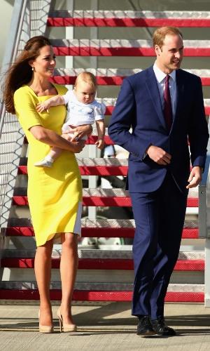 16.abr.2014 - Kate Middleton e Príncipe William desembarcam com o filho, o Príncipe George, no aeroporto de Sidney, na Austrália, após deixarem a Nova Zelândia. Durante o voo, a Duquesa de Cambridge, que embarcou com um conjunto azul, trocou de roupa e deixou o avião com um vestido amarelo. O casal está em viagem pela Oceania, a primeira oficial de George
