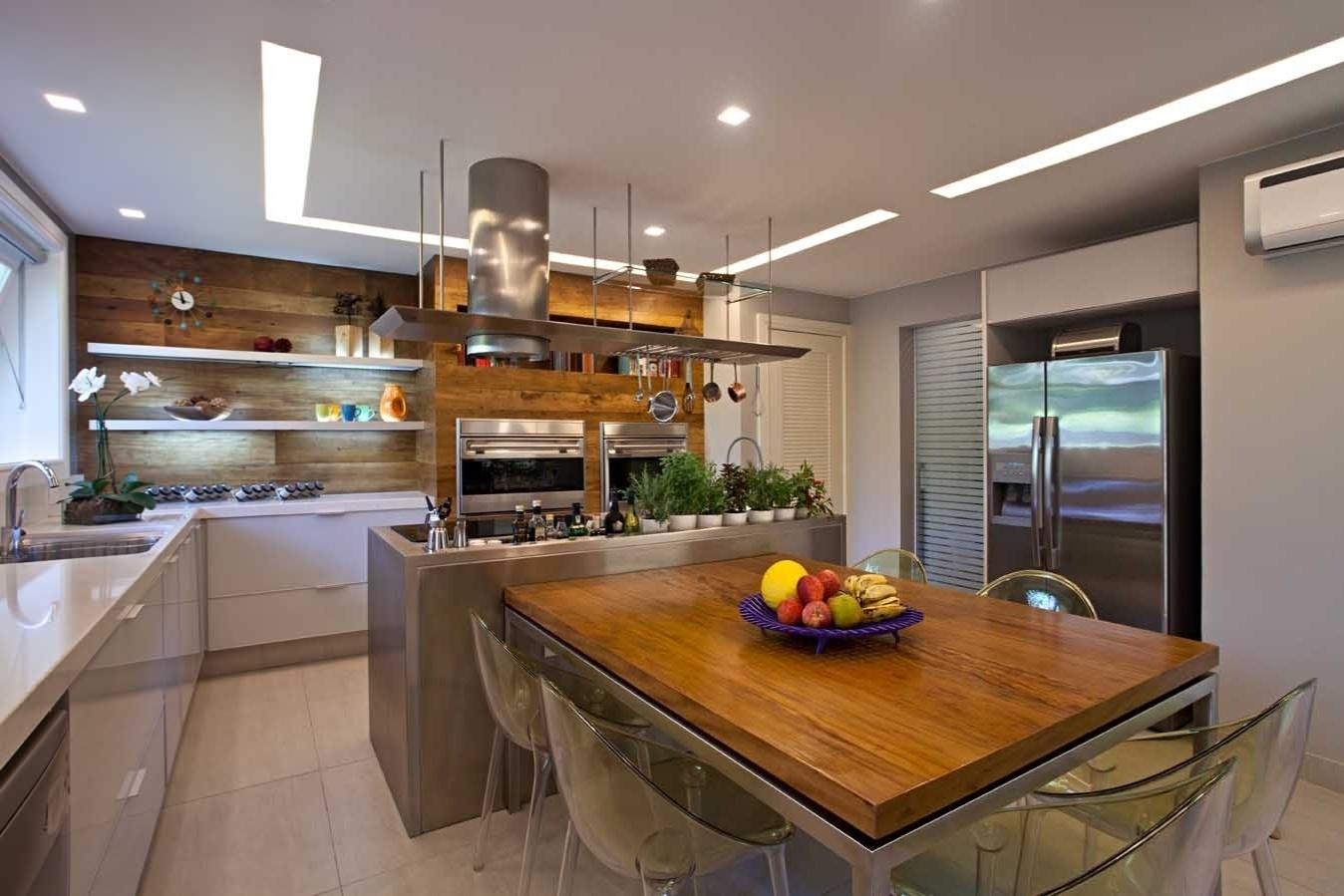 A arquiteta Andrea Chicharo criou um projeto de cozinha em que o cozinheiro permanece no centro do ambiente e a mesa de refeições sai da própria bancada de trabalho em aço escovado. Assim, a interação é inevitável