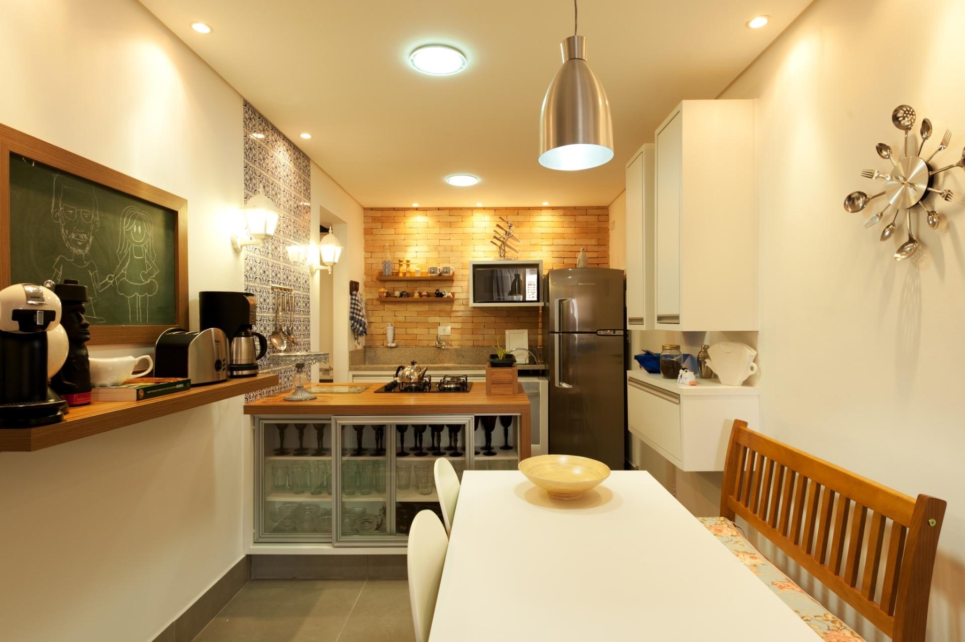 A cozinha dos arquitetos Lucas Sonnewend e Natália Traunmüller preza pela descontração e rusticidade. A parede de tijolinhos contrasta com a modernidade dos eletrodomésticos em inox, enquanto o colorido vem dos azulejos portugueses